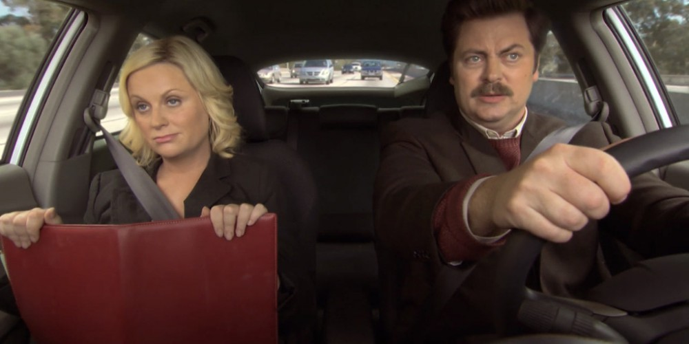 Ron Swanson and Leslie driving in the car.