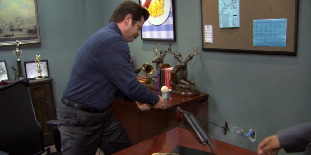Ron Swanson pulls the telephone out of the wall.