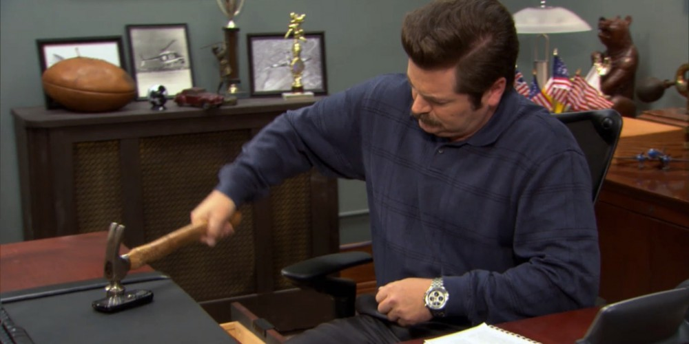 Ron Swanson smashes a cell phone with a hammer.