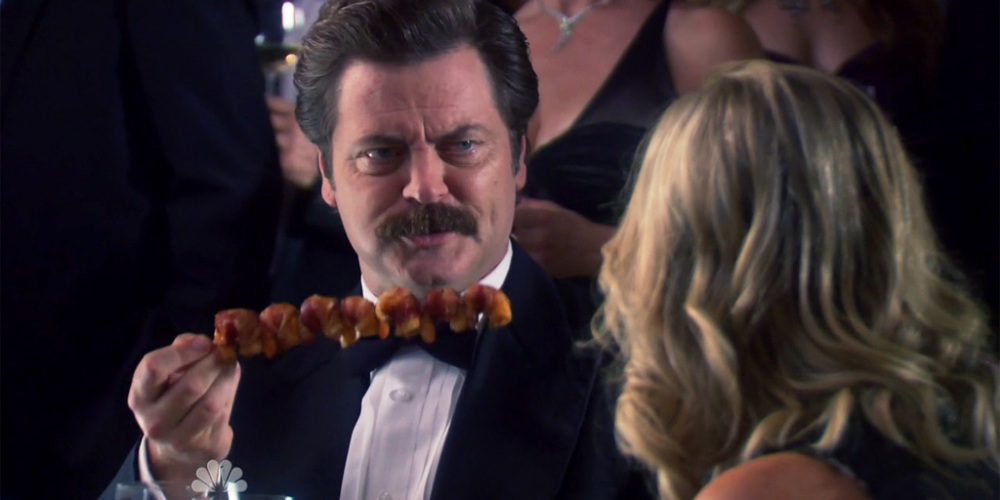 Ron Swanson with his masterpiece skewer of bacon wrapped shrimp